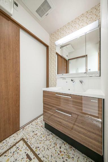 洗面化粧台 収納豊富で使い勝手良好な三面鏡化粧台を採用。アクセントクロスやデザインCFを採用し、目を引く空間に!