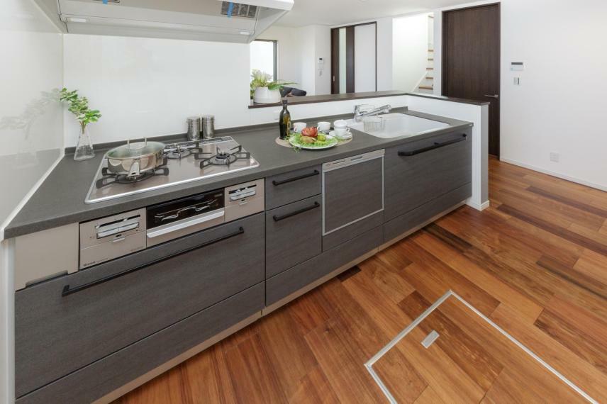 キッチン 【2号棟キッチン】キッチンワークを軽減する食器洗い乾燥機が標準装備。ビルトイン型なので、食器類は出し入れしやすく使い勝手に配慮された嬉しい設備が家事の時間短縮をサポートします。浄水機能付ハンドシャワー水栓はヘッドが引き出せるので、シンクの隅々までキレイにお手入れができます。カウンタートップは耐久性がありお手入れが簡単で、美しい見た目が魅力の人造大理石を採用。