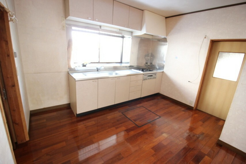 居間・リビング 母屋DK 限られたスペースを有効活用できる壁付キッチンです。東側には土間が備わっています。常温保存の野菜保存や荷物の運び入れにも便利ですね。