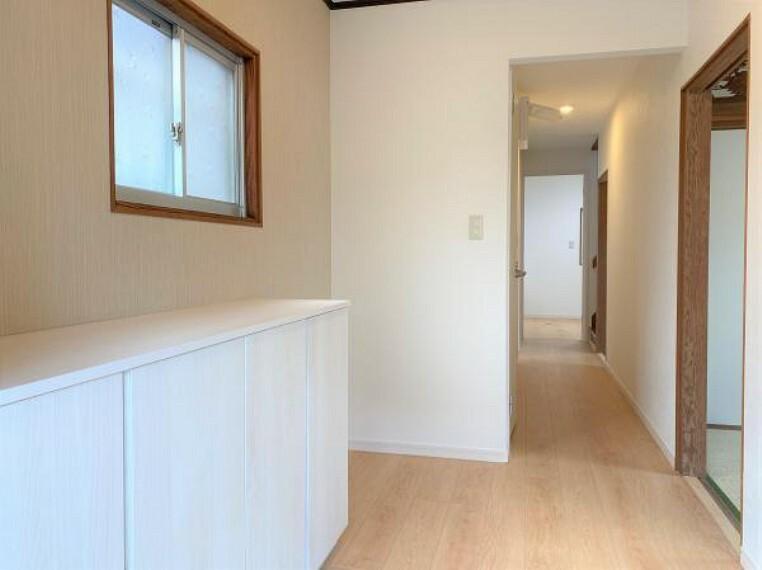 【リフォーム済写真】廊下の写真です。壁天井クロス張り替え、フローリング張り替えを行いました。クロスの白と明るい床材で明るい雰囲気ですね。