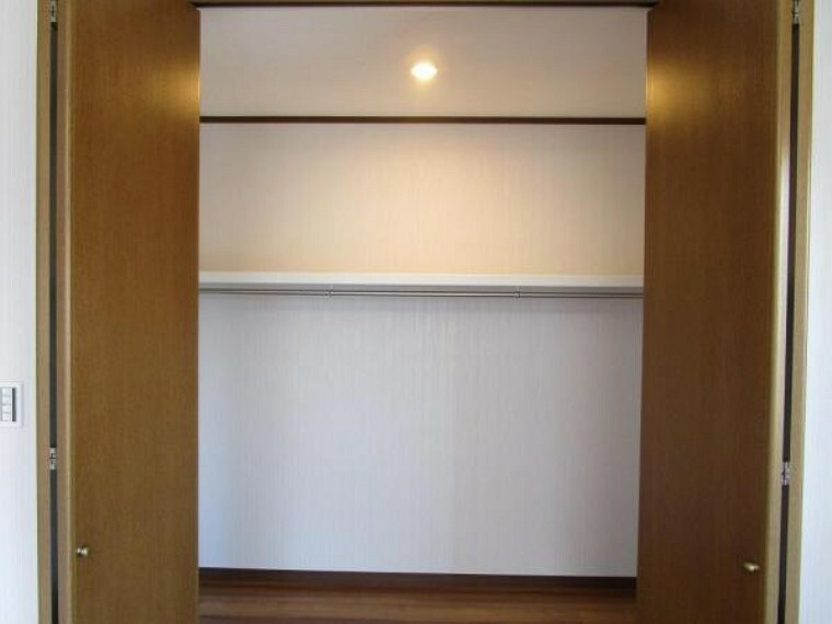 【リフォーム済写真】10.5帖の洋室にあるクローゼットの写真です。ハンガーパイプを設置し、ダウンライトも付けました。お洋服がかけれるだけでなく、バックなども収納できる物置棚がついているので便利ですね。