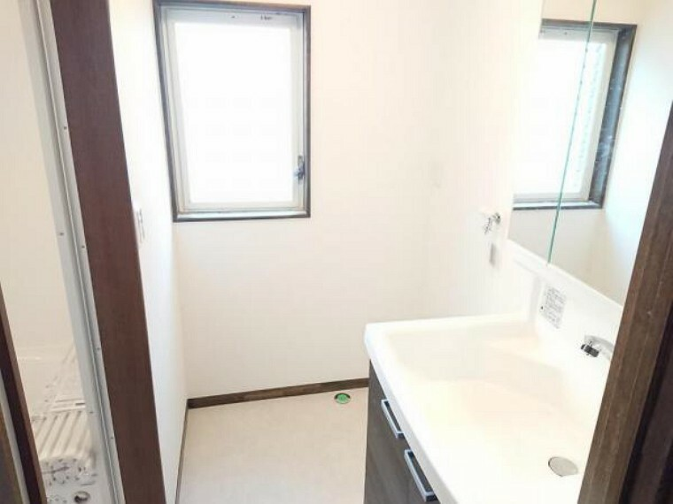洗面化粧台 【リフォーム済】洗面化粧室です。天井・壁クロス張替え、クッションフロア上張り、換気扇・照明・入口建具・洗濯水栓交換を行いました。洗面台の横に洗濯機を置けるスペースがあります。