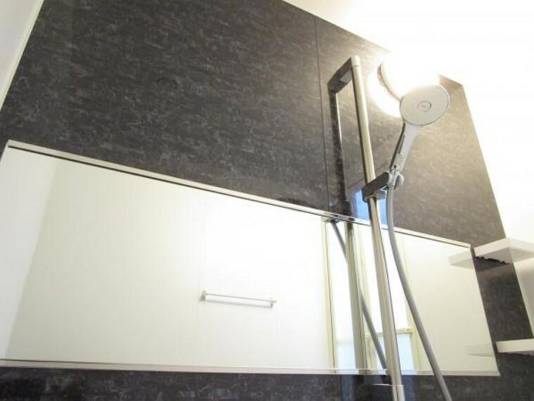 浴室 【リフォーム後写真】新品のユニットバスは高級感のあるアクセントパネルが特徴です。鏡は見やすいワイドタイプです。シャワーヘッドは高級感のある幅広デザイン。新品の浴室で日々の疲れを癒せそうです。