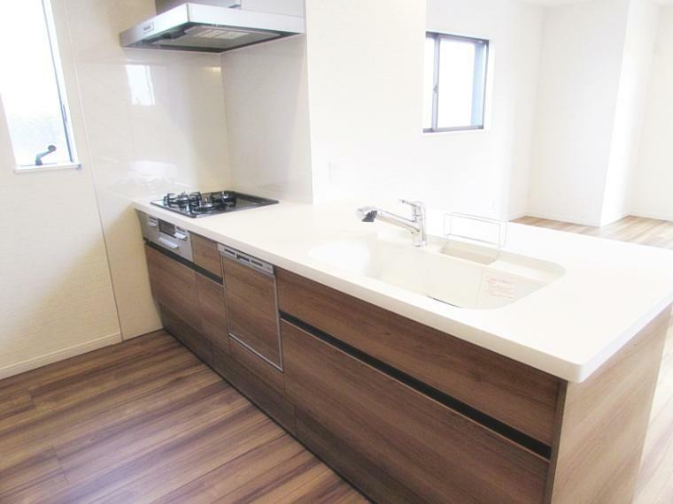 洋室 新築施工事例です。A号地はカウンタータイプのキッチンを採用しています。三ツ口のガスコンロや食洗機、広いシンクのシステムキッチン。