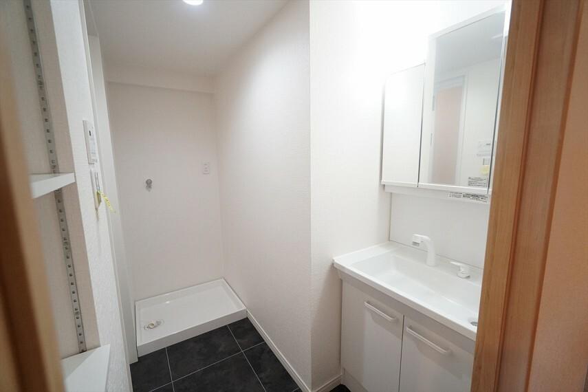 洗面化粧台 明るく清潔感のある色調の洗面室は、 機能性に富んだ三面鏡の洗面台が特徴です  洗濯機置場も完備し、家事の動線が配慮されたデザインになっております。
