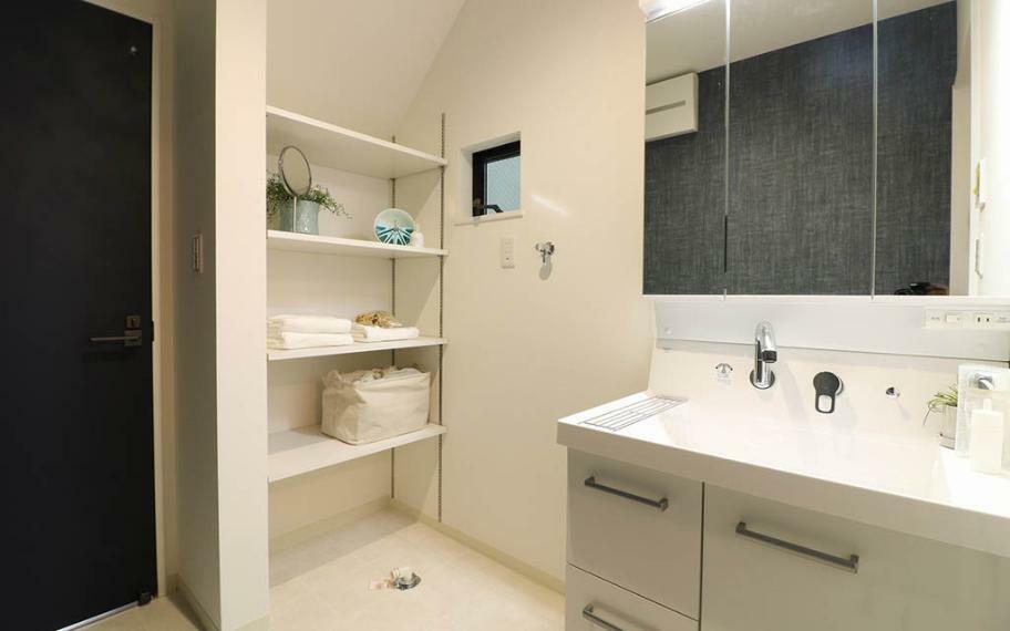 洗面化粧台 タオルや洗剤などの日用品のストックを収納できるように、デットスペースには便利な可動棚を設置しました。