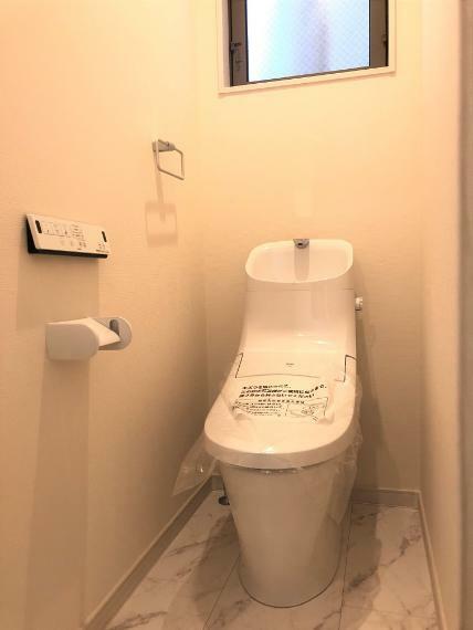 トイレ E号地の2階トイレ写真になります。こちらはベーシアシャワートイレで、左側の紙巻器上に壁リモコンが付いております。