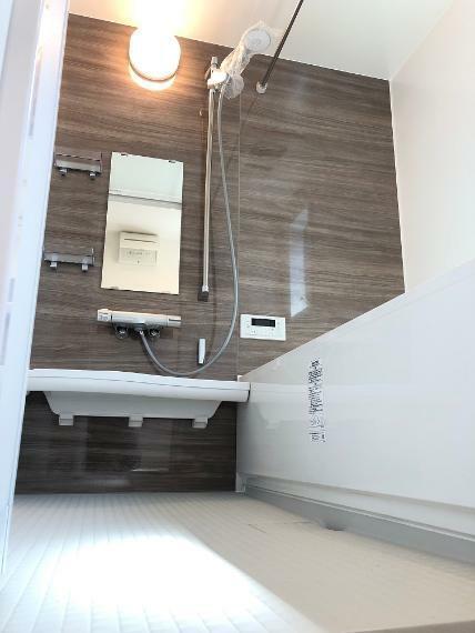 浴室 E号地の浴室写真です。正面アクセントとして、ウォールナットで仕上げました。浴槽は、節水効果のあるエコベンチ浴槽になります。また浴室乾燥機とランドリーパイプも付いているので、洗濯物を乾かすことも可能です