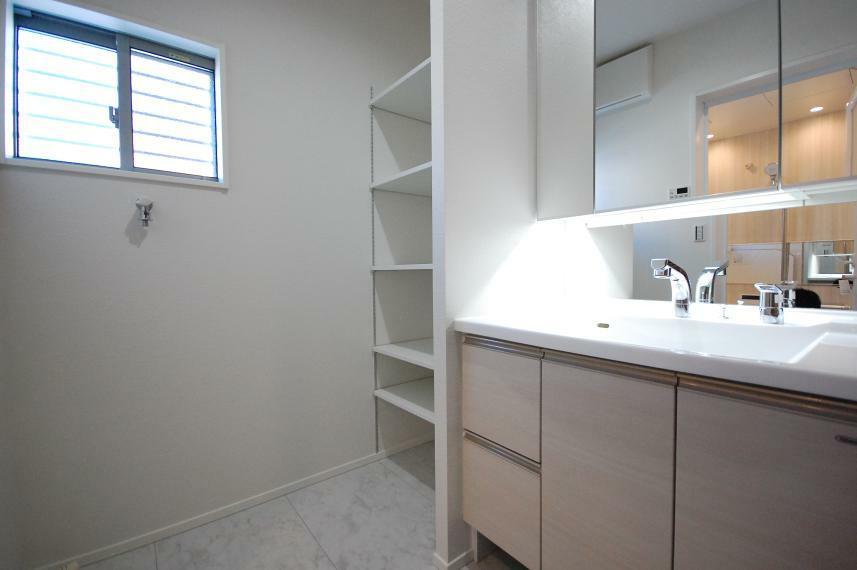 脱衣場 C棟 タオル類なども収納できるランドリー収納あり! ワイドな洗面化粧台で、あわただしい朝の身支度もスムーズに。使いやすいシャワー水栓つきで、大きな三面鏡裏にも収納スペースを作りました。