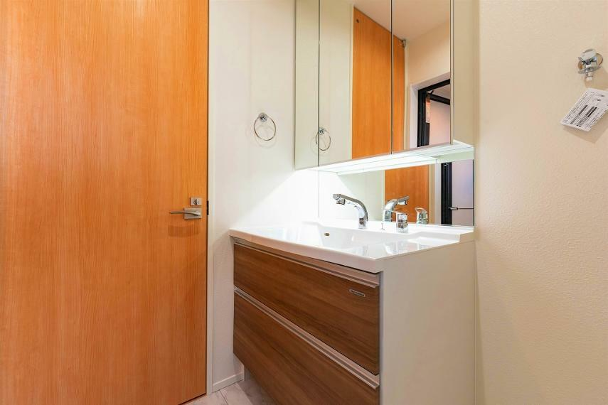 洗面化粧台 大きな3面鏡のついた、広々としたの洗面化粧台。足先が入る空間はヘルスメーターの定位置にも。