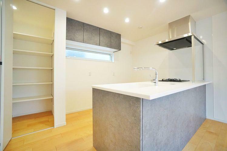 キッチン デザインが美しいカウンタータイプのシステムキッチン。背面にはパントリー付き。
