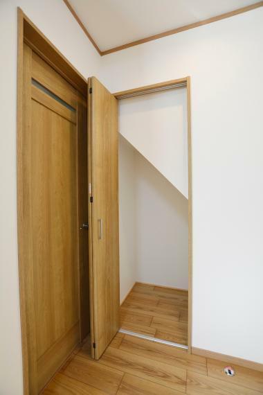 収納 階段下のデッドスペースを利用したリビング収納。洗面・浴室のそばなので、洗面用品の収納にも便利。
