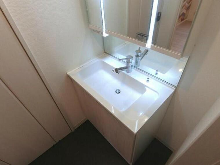 洗面化粧台 清潔感のある洗面脱衣室。朝の支度にも便利な三面鏡付きの洗面化粧台です。