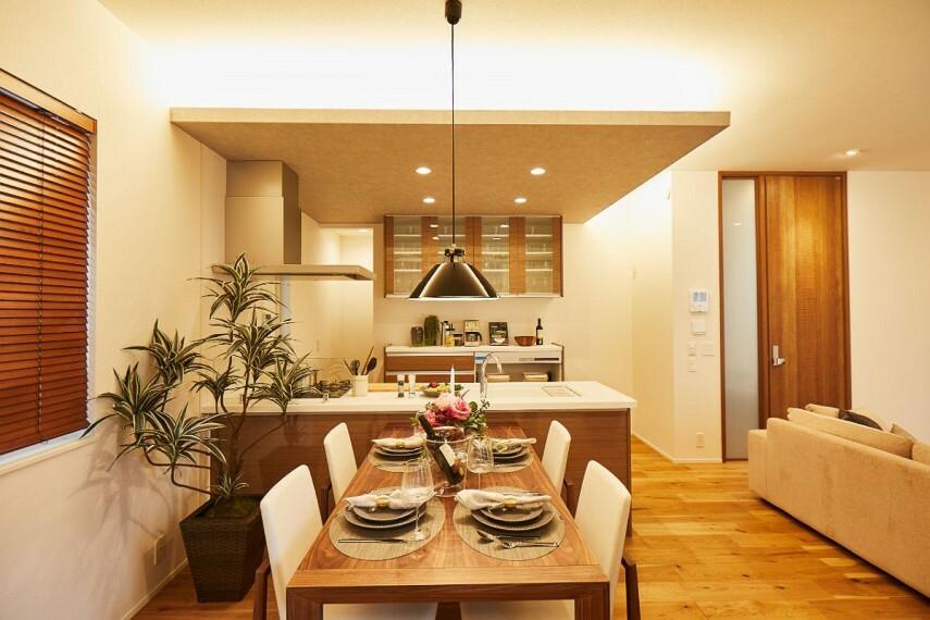 居間・リビング 【ダイニングスペース】  キッチンには折り下げ天井を配し、間接照明がダイニングに立体的な陰影をもたらします。毎日の食卓がレストランのように演出され、食事を愉しむことができます。/PLAN1モデルハウス