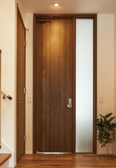【高さ2.7mのリビングドア】  リビングドアは、天井高2.7mまでの高さがあるタイプを採用。重厚で無駄のないその佇まいが、邸宅感を醸し出し、扉の奥への期待感が膨らみます。