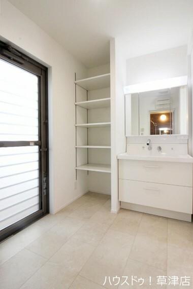 洗面化粧台 洗面台横にはタオルなどを収納できるスペースもあり、勝手口もあります。
