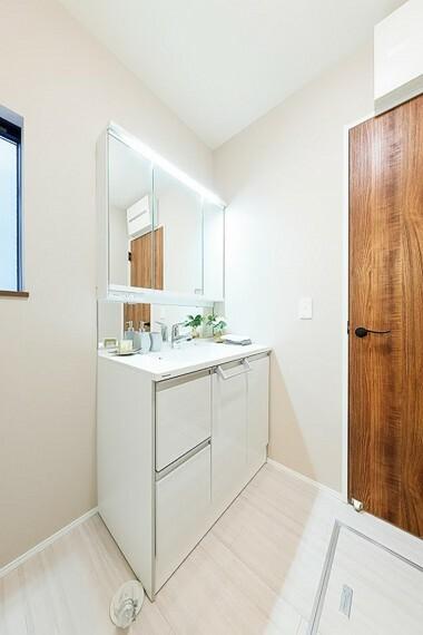 洗面化粧台 モデルハウス1号棟/洗面所  木の質感のドアがアクセントの白の清潔感ある洗面所です。収納棚付きで利便性もいいです。(※2021年2月撮影)