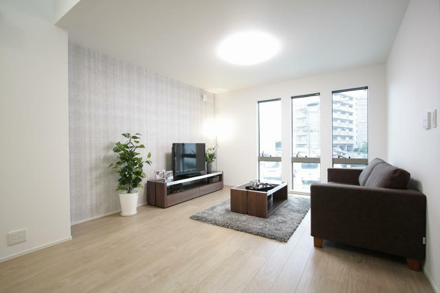 居間・リビング A棟モデルハウス リビング : 3連窓とアクセントクロスの壁が落着きのある雰囲気を演出。