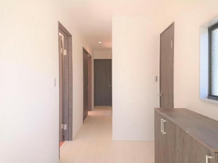 【リフォーム済】廊下の写真です。廊下もフローリングの重ね張りとクロスの張替えを行いました。白のクロスを張り、明るい印象の廊下に生まれ変わりました。