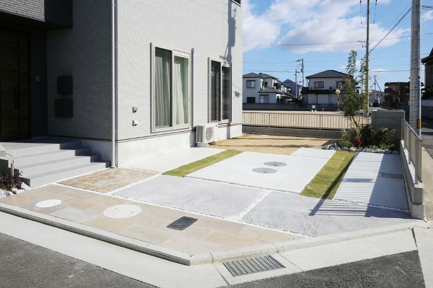 現況外観写真 【芝生を配した駐車スペース】 駐車場スペースには、芝生を配した緑を感じる外構コーディネート。住まう方はもちろん訪れるゲストも気持ちよく迎えます。