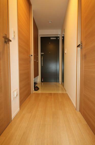 玄関 優しい色合いの建具や床材で統一された室内。