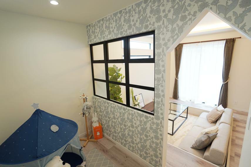 居間・リビング リビング横にはキッズスペースがあります。入り口の三角垂れ壁がアクセント。仕切り壁のデコ窓で開放感のある空間に。