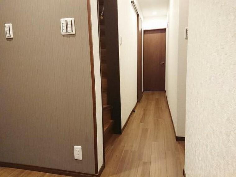 【リフォーム済】1階廊下写真。天井・壁はクロス貼替え、床はウッドタイルで仕上げました。照明器具も全て新品に交換し、広く明るい廊下に生まれ変わりました。