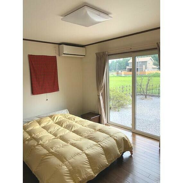 約8帖の居室。大きなベッドをおいても余裕ある広さ。