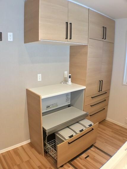 キッチン No.82-18_カップボード(撮影_2021年3月)リビングとの調和もとれる優しい木目調の扉。ダストボックスワゴンはすっきり収納。床下収納庫も付きます。