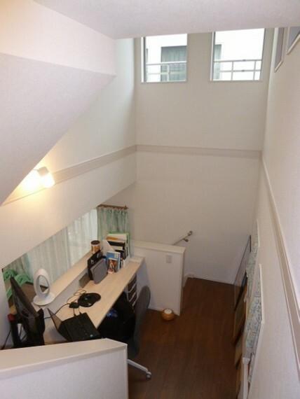 スキップフロアの階段から、吹き抜けと、書斎と、リビングの方向を撮影したものです。吹き抜けから光が入り、テレワークの書斎からリビングが見下ろせます。