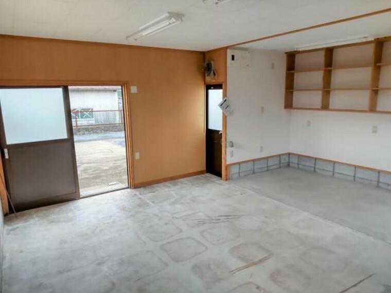現況写真 【リフォーム後写真】東側倉庫室内写真です。事務所としても充分お使いできる広さがあります。収納棚も設置されています。電動シャッター付きなので防犯も安心です。
