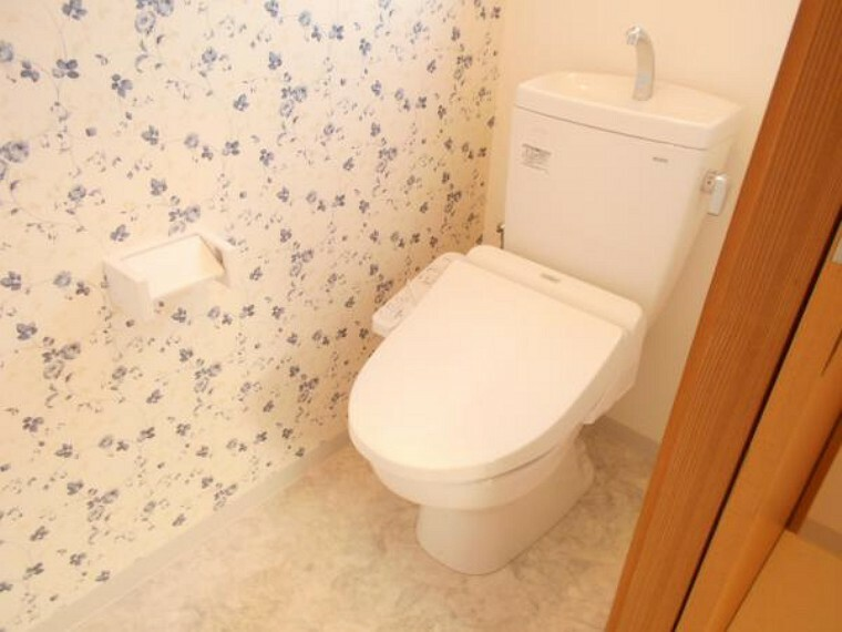 トイレ 【リフォーム後写真】TOTO製のウォシュレット付きトイレに新品交換しました。壁面のワンポイントクロスが華やかですね。節水、節電機能付きで環境にもお財布にも優しいトイレです。気になる水回りが新品だと嬉しいですね。