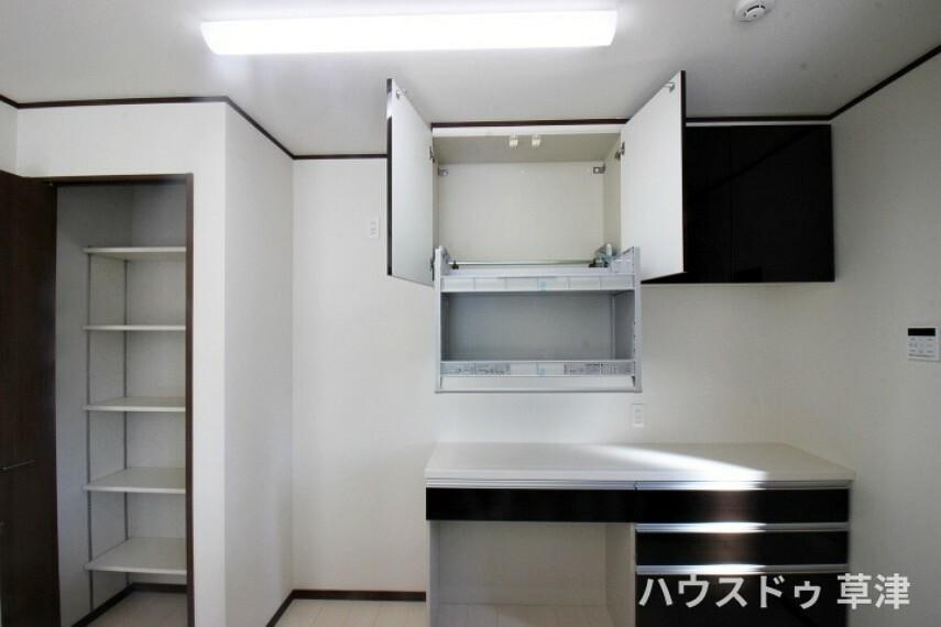 キッチン キッチンにはカップボード付きです。ムーブダウン吊戸棚でデッドスペースなく収納ができ便利です。収納した物を取り出しやすいのも特徴です。その横には収納棚もありストック品などたくさん収納出来ます。