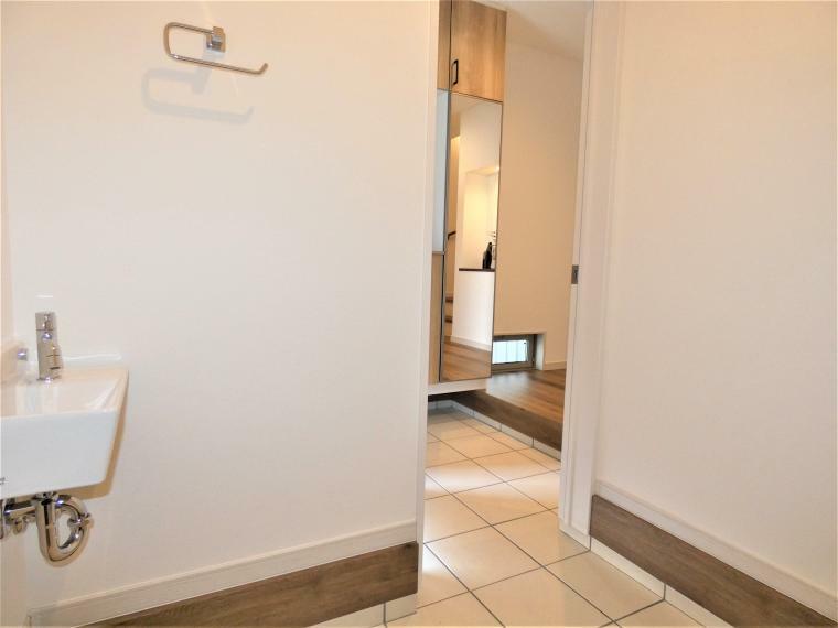 同仕様写真(内観) 玄関横には大型シューズインクロークを設けいつでも広々玄関をキープ。お子様の遊び道具やご趣味の用具の収納など用途たっぷり。エチケットスペースを設け手洗いうがいが習慣づく手洗いを設置。