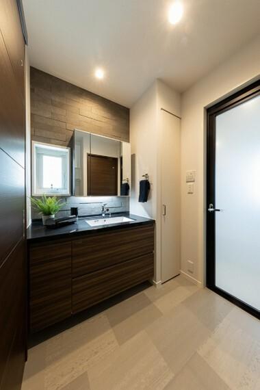 洗面化粧台 No.53_洗面脱衣室(撮影_2021年4月)3面鏡洗面台の天板はフィオレストーンを採用。スタイリッシュなデザインが脱衣所も美しく演出してくれます。脱衣所収納も完備。