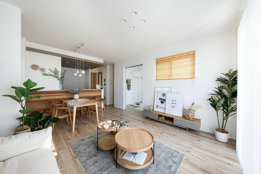 居間・リビング 【家族のシーンを美しく彩る家】  LDK17.75帖の開放的な空間は、ワイドサッシから陽光が差し込み、室内全体を柔らかな雰囲気に。キッチンと畳フラットには素材の異なる木のインテリアを施すことで、個性を演出しています。/12号棟モデルハウス(2020年11月撮影)