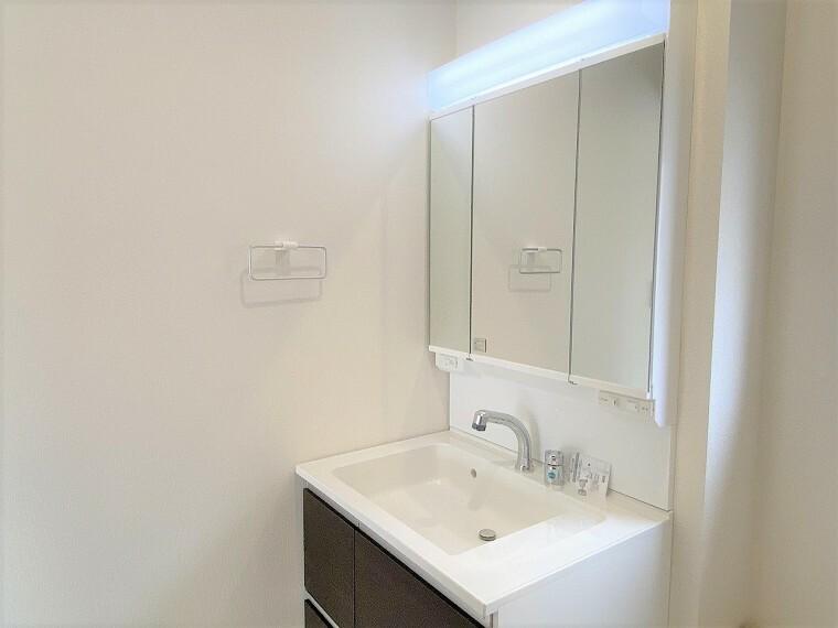 洗面化粧台 小物収納もたっぷりのワイドな三面鏡シャンプードレッサー 朝の身支度もラクラクですね  脱衣所は窓付きで明るい印象