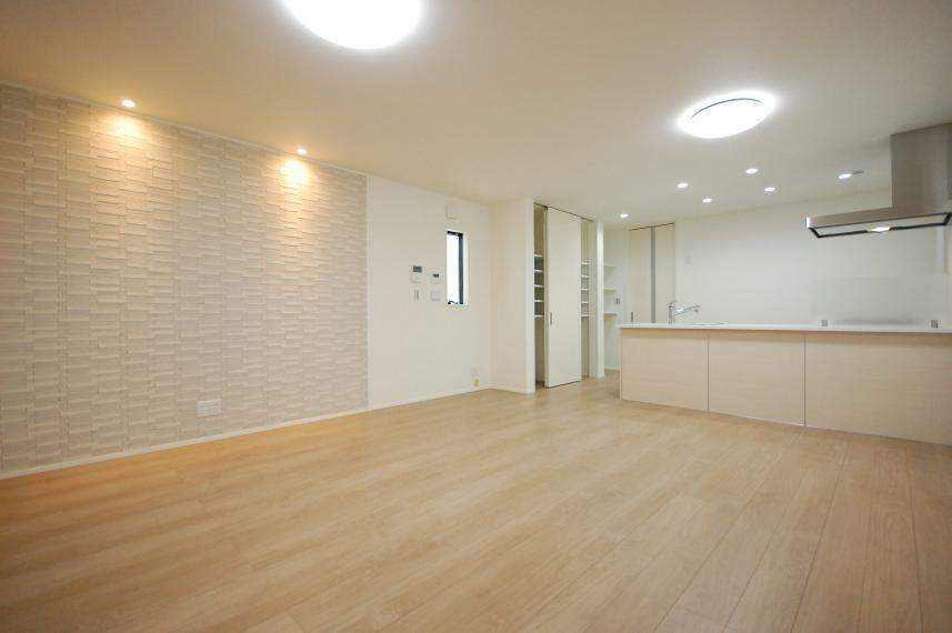 居間・リビング A棟リビング/明るい木目でコーディネートされたA棟。壁面を照らすダウンライトがエコカラットの凹凸を際立たせ、リビングを温かい雰囲気に包みます。