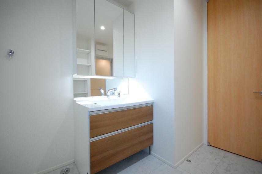 洗面化粧台 B棟/洗面台の大きな三面鏡はくもり止めヒーターとコンセントを搭載、鏡の裏は隅々まで収納になっています。タオルや化粧品を一時置きできる横幅90センチのワイドなカウンター。