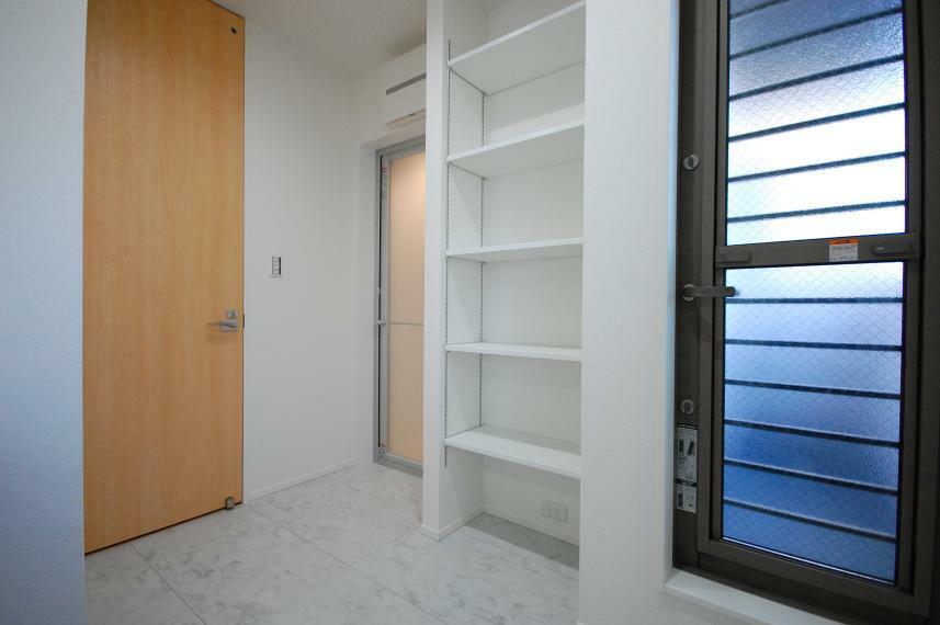 ランドリースペース B棟/洗面室には作り付けの収納棚と、北面バルコニーへの勝手口があります。タオル類を干したら収納棚までほんの数歩、家事動線良好です。