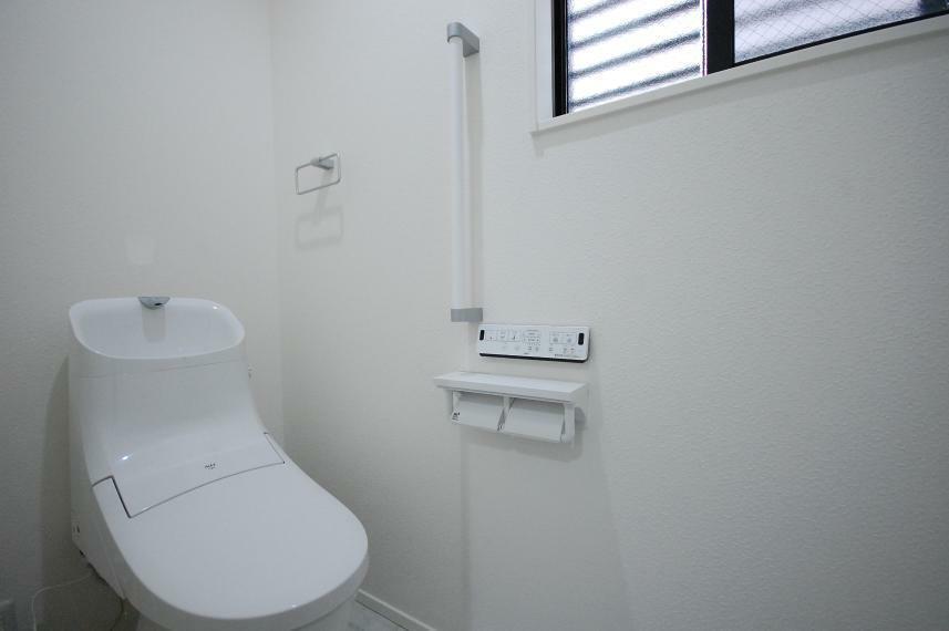 トイレ A棟1階/立ち上がると自動で洗浄するフルオート洗浄や、便座がゆっくり閉じるスローダウン機能つき。将来を見据え、立ち上がり動作を助ける「縦手すり」を標準設置しています。
