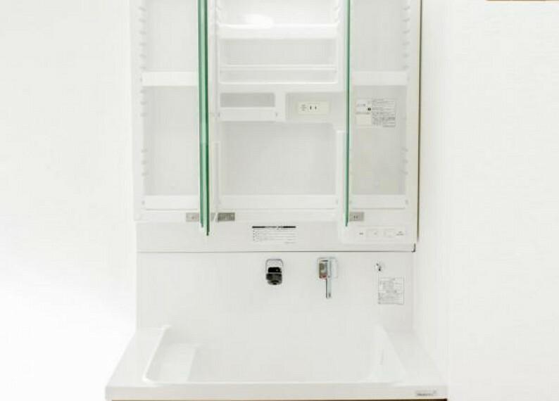 洗面化粧台 【リフォーム済】洗面台の鏡は三面鏡タイプで内部が収納棚になっています。収納の内部にコンセントがあるので電動歯ブラシや電気シェーバーなどは充電したまま収納することができます。
