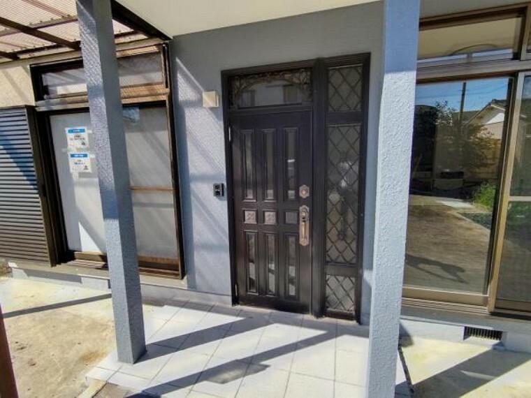 駐車場 【リフォーム済】玄関扉の写真です。玄関扉はクリーニング、鍵交換、タイル張替え、照明交換を行いました。スッキリとした玄関に生まれ変わりました。外壁のターコイズブルーがメリハリをつけた印象になっていて、毎日飽きがこない玄関ですね。