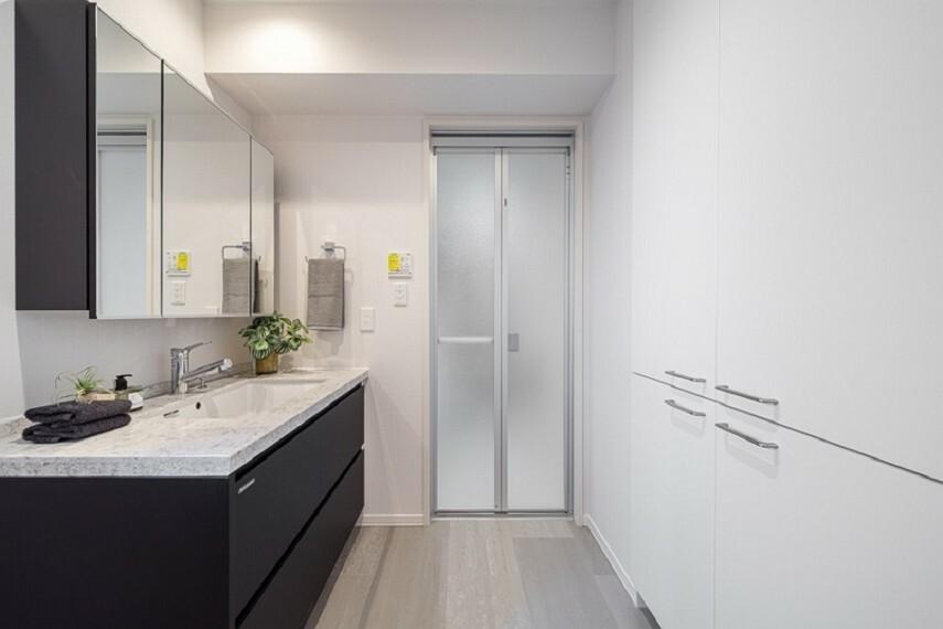 洗面化粧台 No.7_洗面脱衣室(撮影_2021年3月)3面鏡洗面台の天板はフィオレストーンを採用。スタイリッシュなデザインが脱衣所も美しく演出してくれます。脱衣所収納も完備。