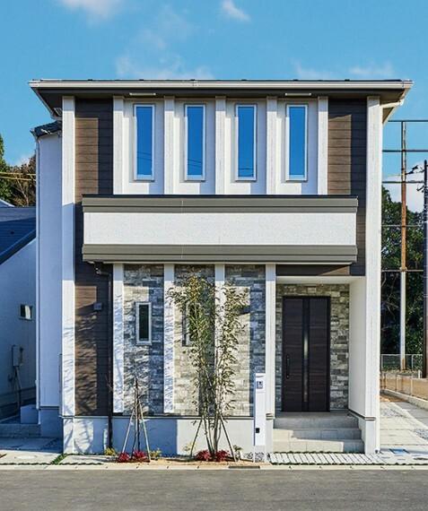 現況外観写真 【VERTI CAL Style】  窓や柱、縦のラインを特徴としたスタイル。木目や石のブラウンカラーに映える白い縦柱。街行く人々の目に留まる印象的なデザインです。/2021年2月撮影
