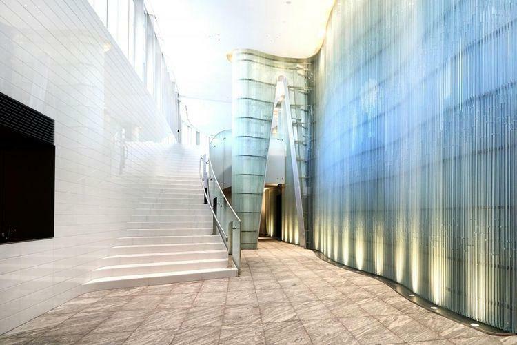 エントランスホール Entrance  吹抜けのグランドエントランスには、エマニュエル・バロワ氏によるガラスのアートウォールを配置。曲線の大階段により、光が取り込まれた2階のガーデンラウンジへと訪れる方を誘います。