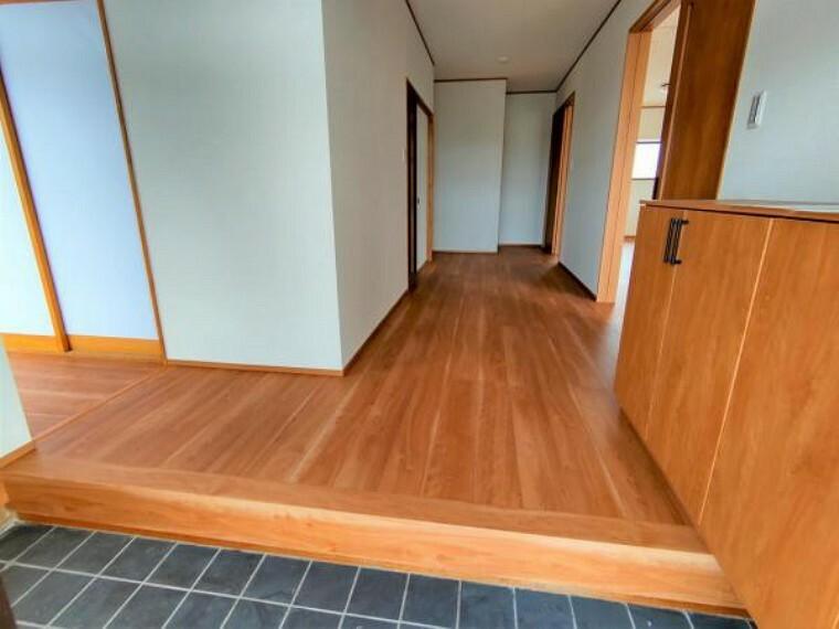 【リフォーム済】玄関ホールから廊下です。床にはフローリングを重ね張りし、照明交換、クロス貼替を行いました。廊下の幅が広いので開放感があって明るい印象です。