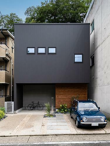 参考プラン完成予想図 【施工事例】 黒いガリウムの外観と、玄関の目隠しとなるレッドシダーの壁の組み合わせがシックな外観。駐車場スペースは、タイヤの跡がつかないようにモルタルの洗い出し仕上げに。