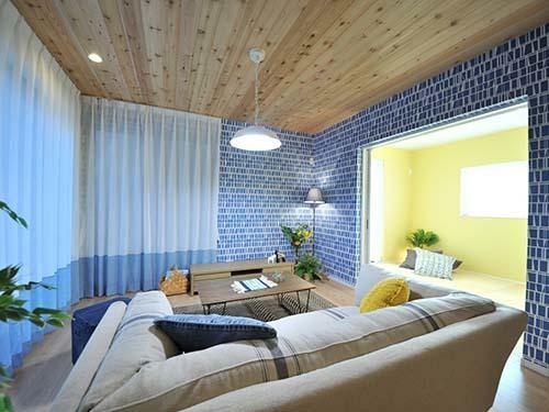 参考プラン完成予想図 【当社施工例】 リビングでは無垢張りの天井と鮮やかなブルーと白のクロス、カーテンでダイニングとは異なる風合いデザイン。明るいイエローの和室とも相性が良い。