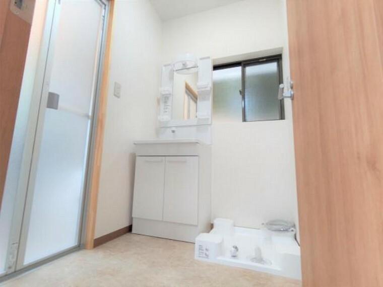 洗面化粧台 【リフォーム中】浴室拡幅に伴い、洗面所も拡張を行いました。洗濯機と洗面台の設置スペースを確保しています。壁と天井のクロス張替、床はクッションフロアで仕上げました。